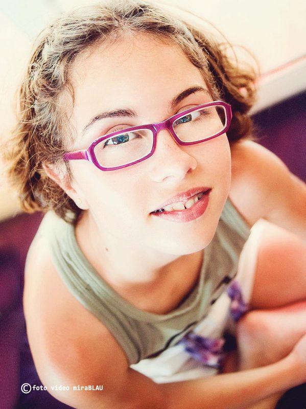 Foto Retrato niña con gafas sentada