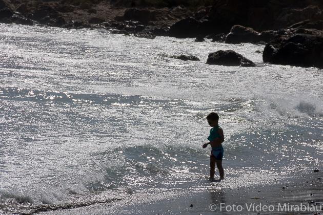 foto Contra luz en la playa. Niño entrando en el mar.