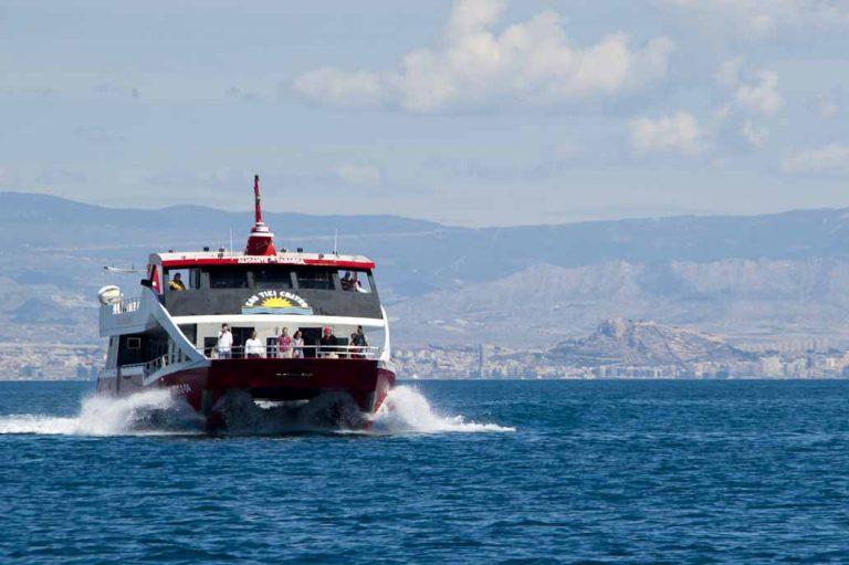Fotografía de promoción turística. Transporte a isla de Tabarka, Tabarkera, con la ciudad de Alicante al fondo.