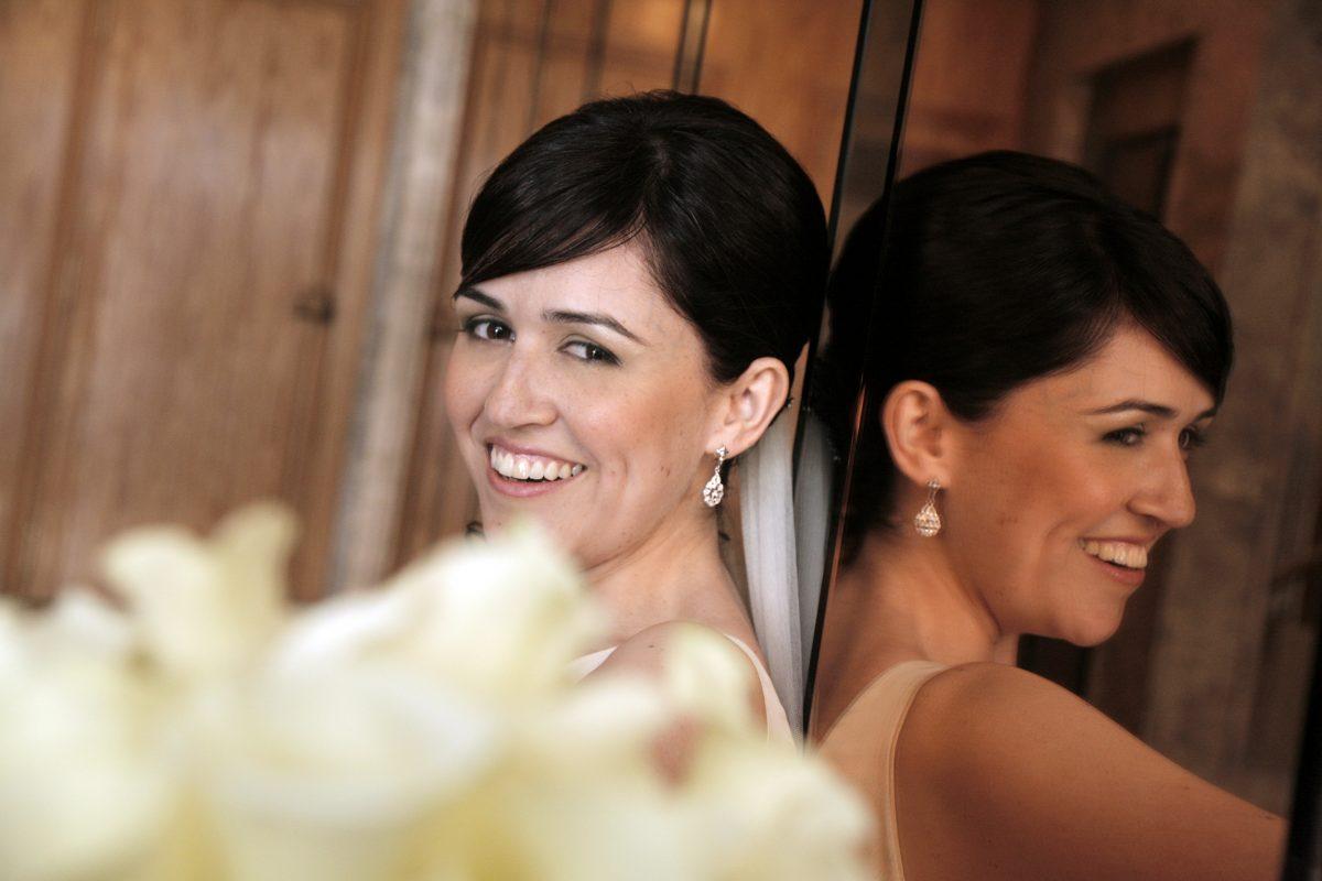 Foto novia apoyada en un gran espejo.