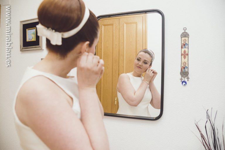 Novia frente a espejo retoca pendientes